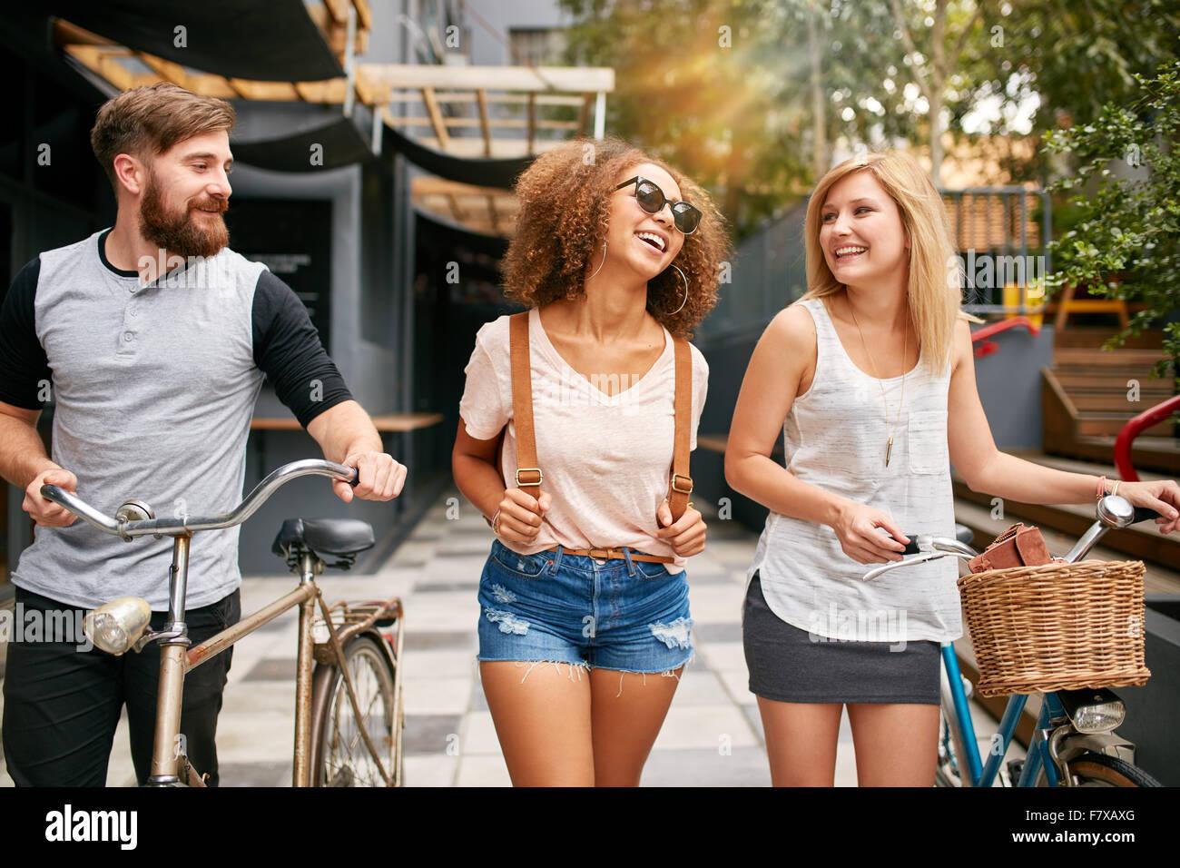 Los jóvenes feliz caminando por las calles de la ciudad con sus bicicletas y sonriente. El hombre y la mujer Imagen De Stock