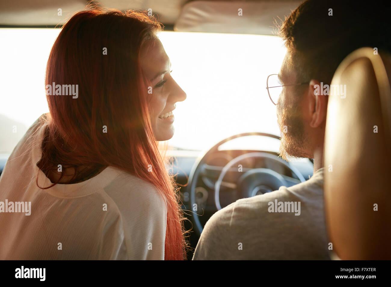 Vista trasera de la joven pareja en un viaje por carretera en un día de verano. Afectuosa pareja joven de vacaciones Imagen De Stock