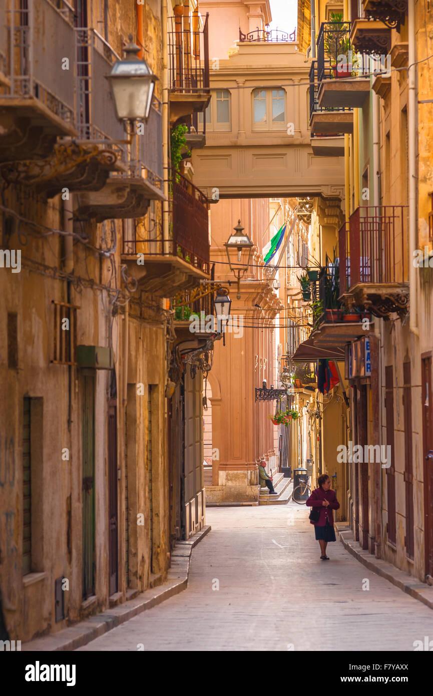 Marsala Sicilia, vista en verano de una mujer mayor caminando sola en la Via Mario Rapisardi en el centro histórico Foto de stock