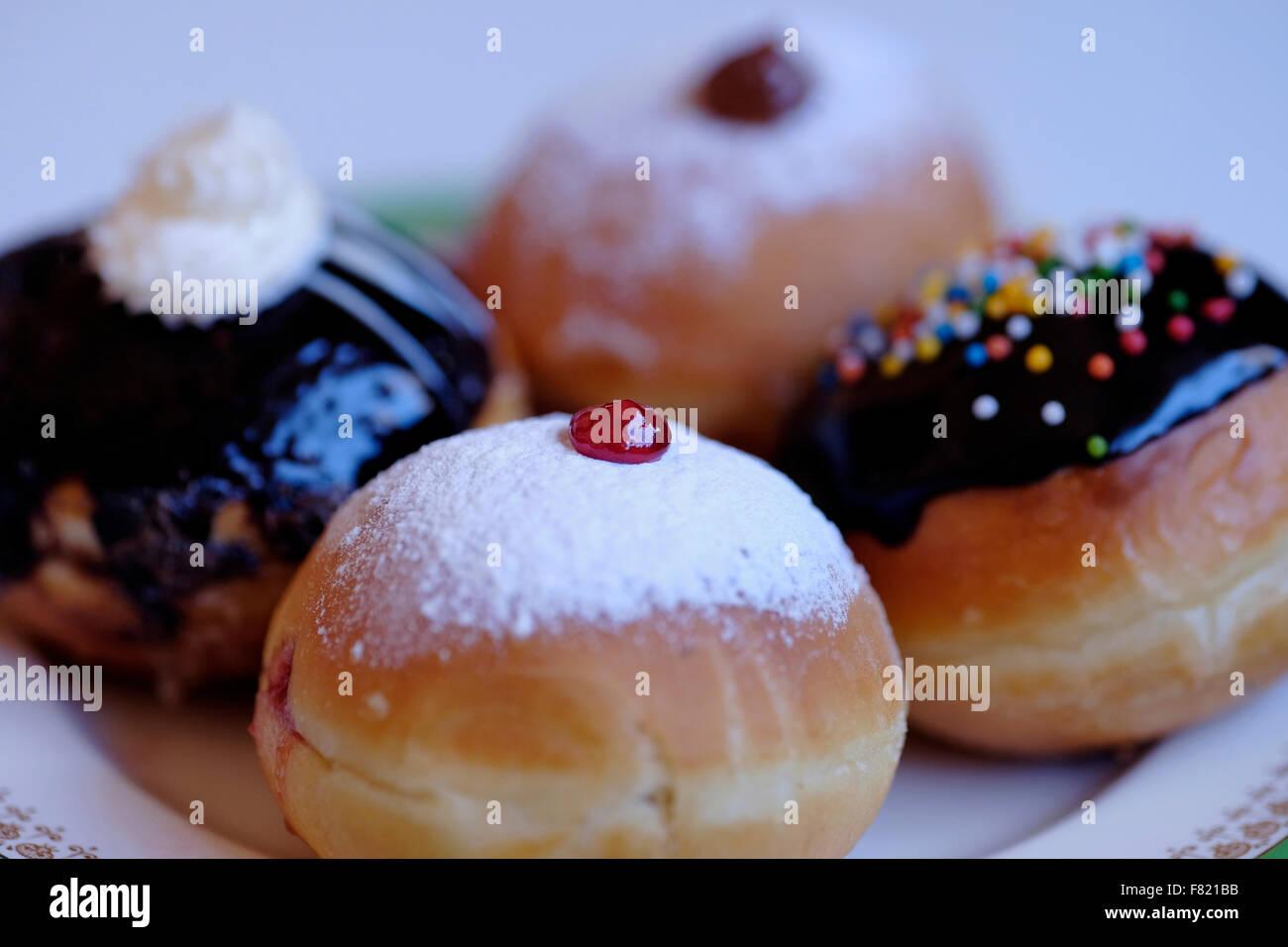 Elegantemente Sufganiyot tradicional frita donut redondo comido durante la fiesta judía de Jánuca Imagen De Stock