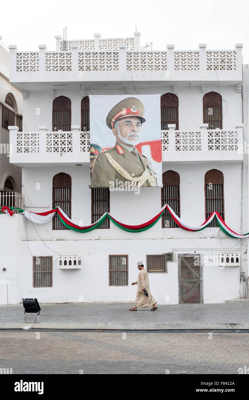 Hombre caminando pasado un edificio adornado con un cartel del Sultán de Omán en Mutrah en Muscat, la Imagen De Stock
