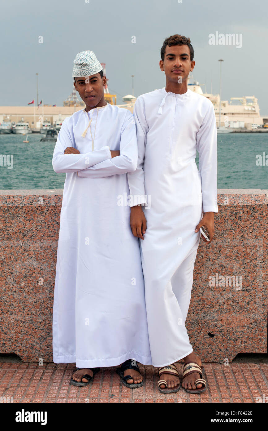 Los jóvenes omaníes, hombres en trajes tradicionales en el Mutrah promenade en Mascate, la capital del Imagen De Stock