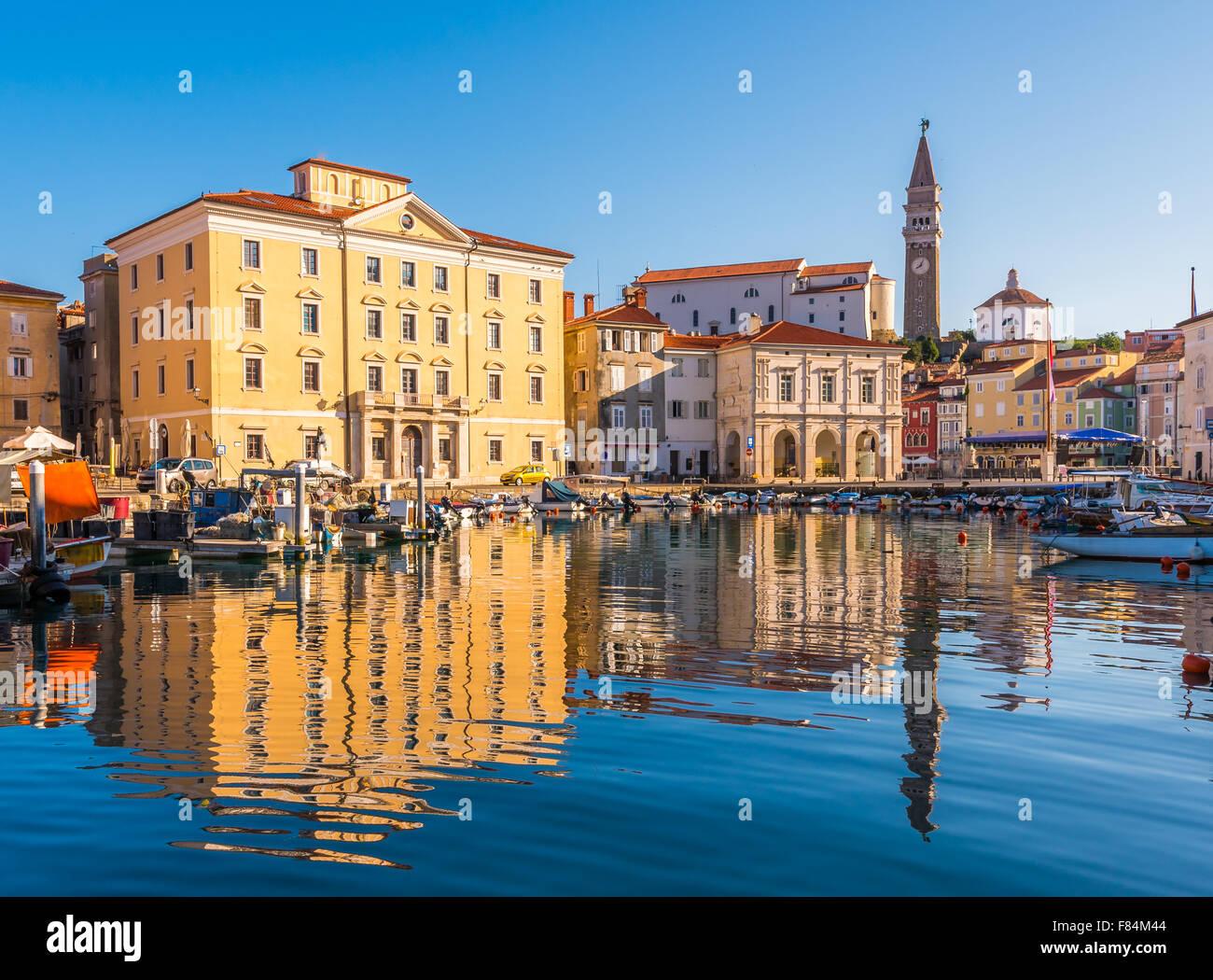 Puerto Veneciano y la plaza principal de Tartini Piran ciudad reflejada en el agua en Eslovenia. Foto de stock