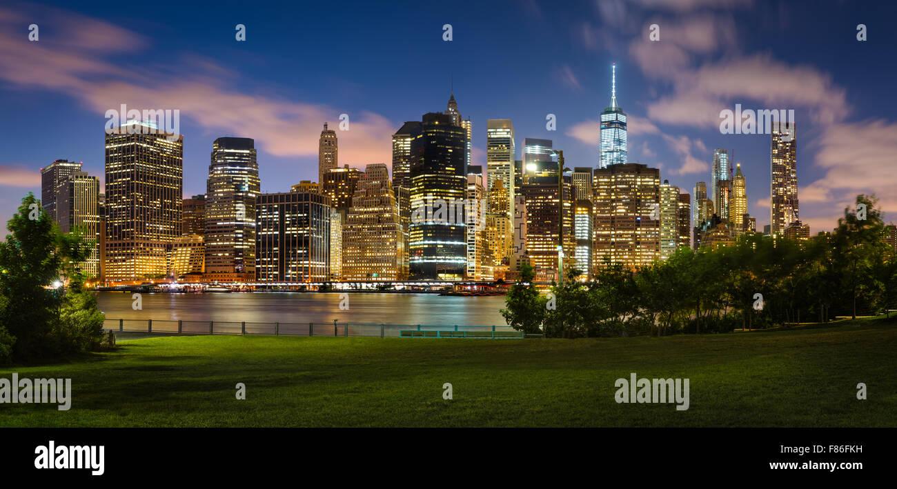Vista de noche de Manhattan, rascacielos iluminados cruzando el Puente de Brooklyn Park. El distrito financiero Imagen De Stock
