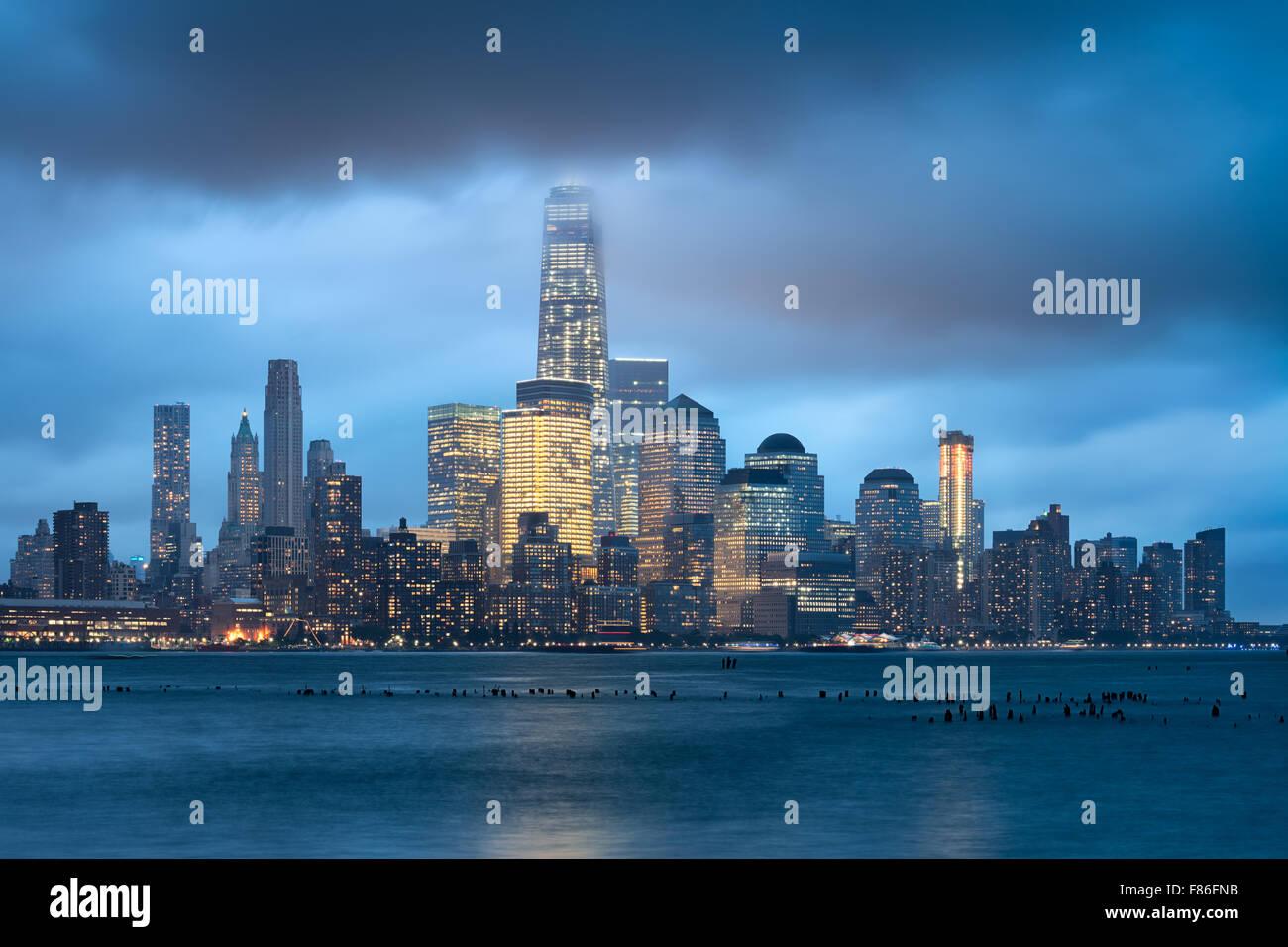 Lower Manhattan y el distrito financiero de rascacielos iluminados con nubes de tormenta, la ciudad de Nueva York. Imagen De Stock