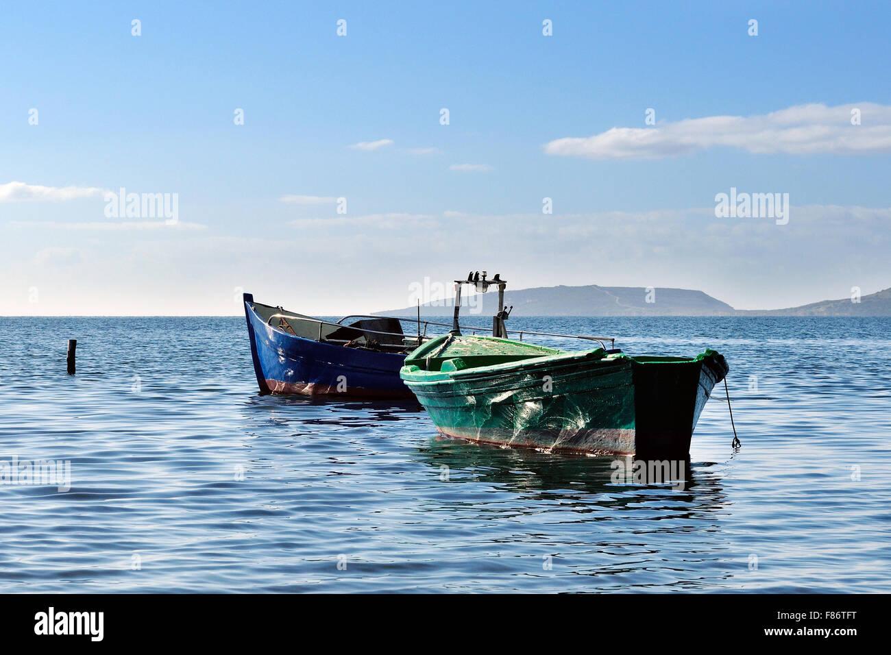 Barcos pesqueros amarrados en el tranquilo mar del golfo de Oristano Foto de stock