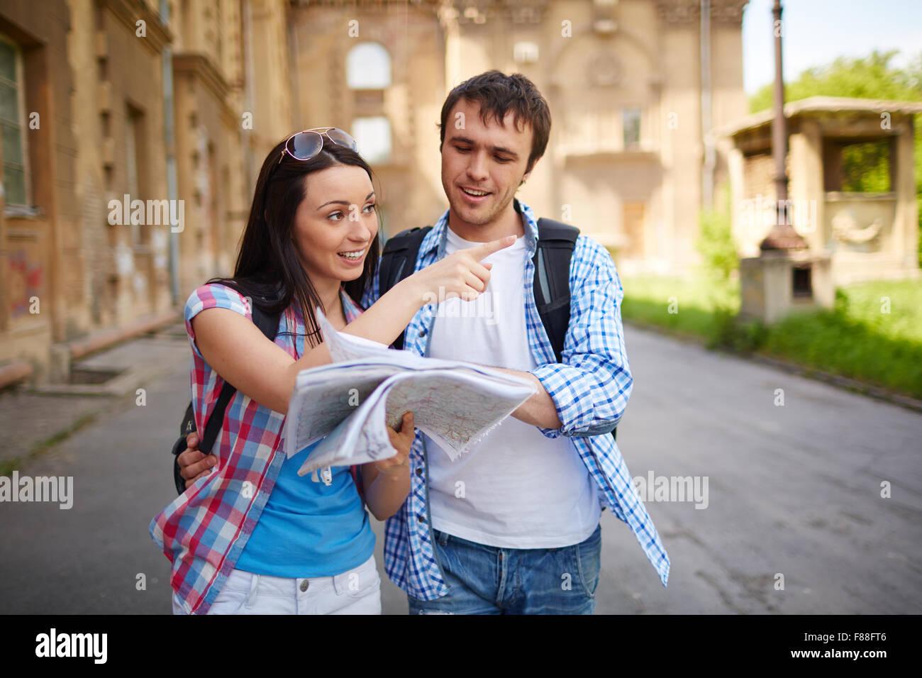 Par de turistas consultar una guía de la ciudad buscando lugares en la calle y apuntando Imagen De Stock
