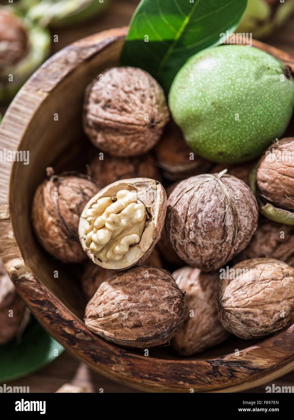 Las nueces en el tazón de madera sobre la mesa. Imagen De Stock