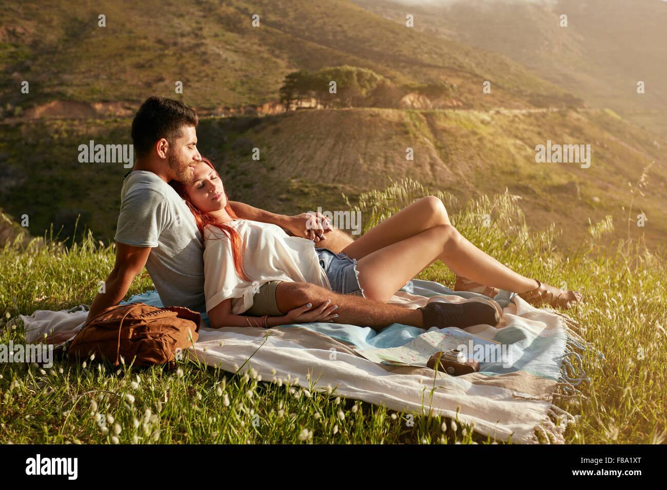 Pareja joven tener un picnic en un prado en un día soleado. Un hombre y una mujer caucásica relajándose Imagen De Stock