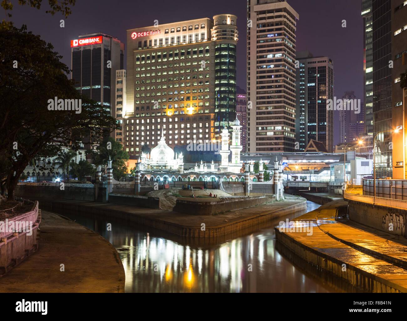 Una vista de noche de uno de los más antiguos de Kuala Lumpur, la mezquita Masjid Jamek y edificios bancarios en Foto de stock