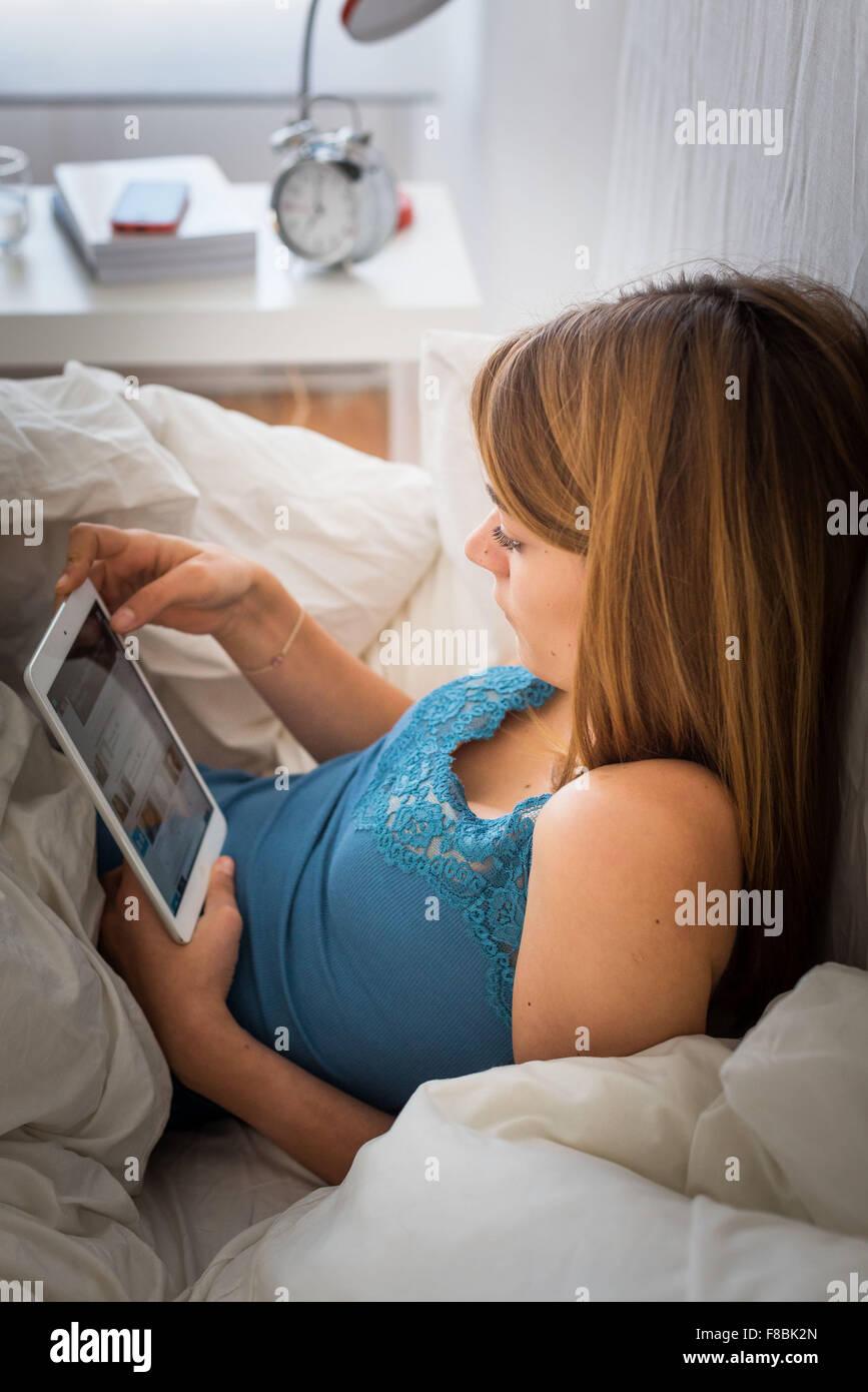 Mujer utilizando una tableta digital acostado en la cama. Imagen De Stock