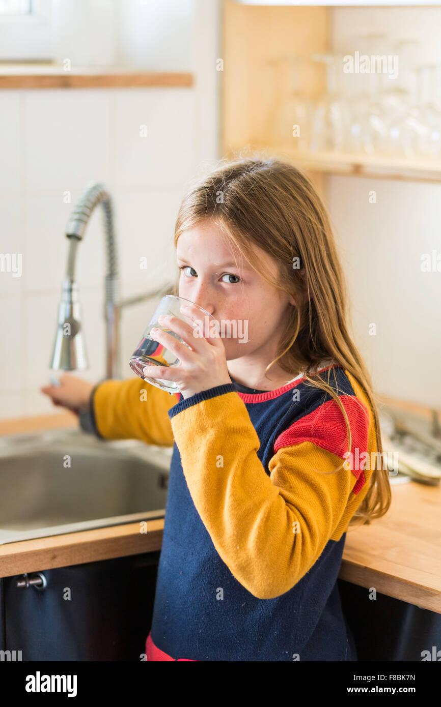Niña de 9 años de beber agua del grifo. Imagen De Stock