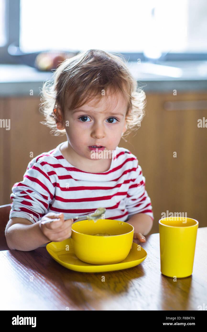 Niña de 24 meses de comer solo. Independencia la capacitación. Imagen De Stock