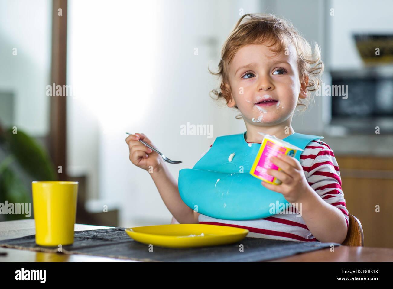 2 años de edad, comiendo un yogur. Foto de stock