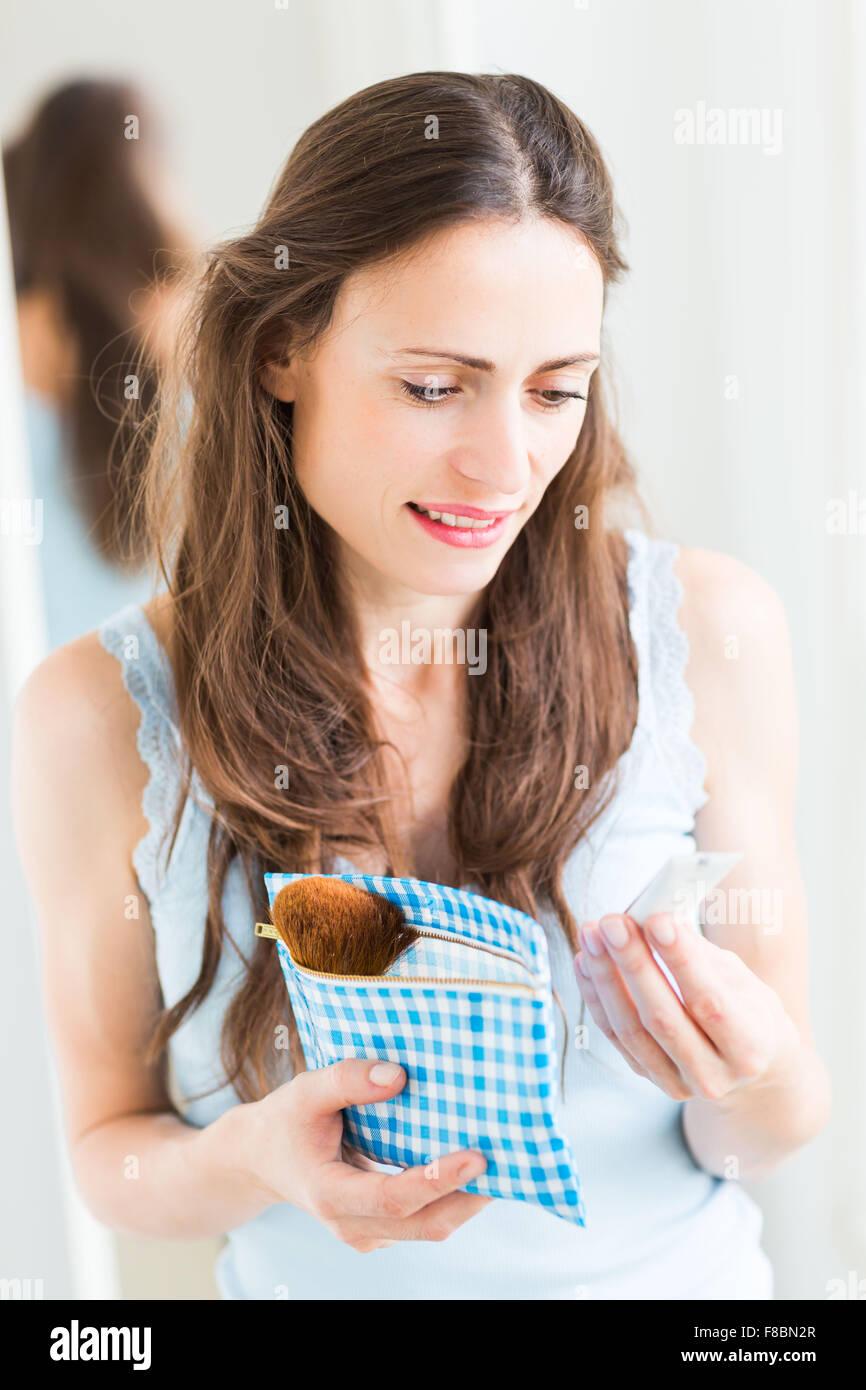 Mujer leyendo la composición del producto cosmético. Imagen De Stock