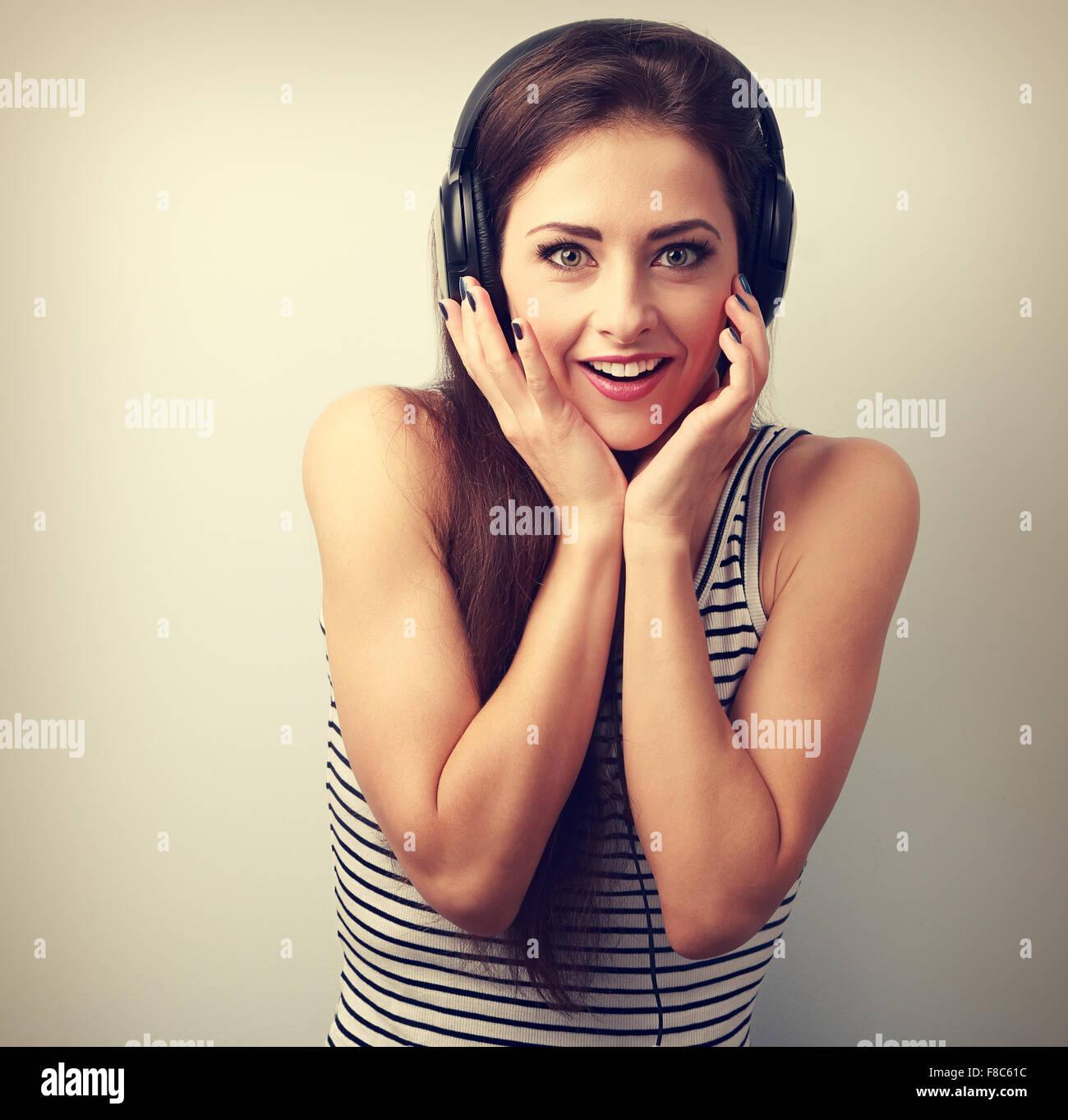 Mujer alegre y sorprendente en los auriculares escuchando la música. Retrato Vintage Imagen De Stock