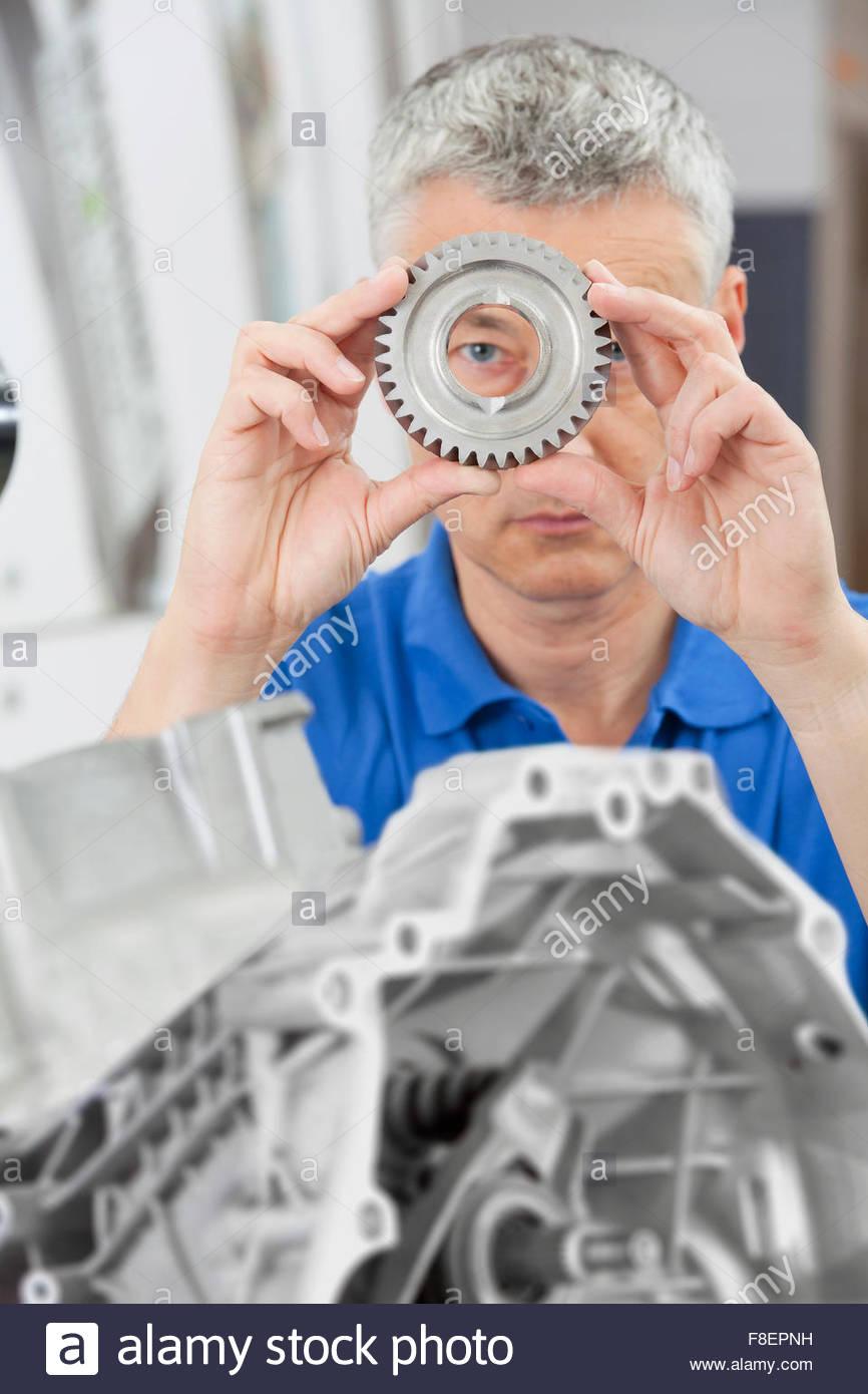 Retrato del ingeniero mirando a través de la rueda dentada con el bloque del motor en primer plano Imagen De Stock