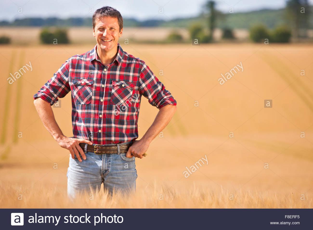 Retrato seguro campesino con las manos en las caderas en un soleado día de campo de cultivos de cebada rural Imagen De Stock