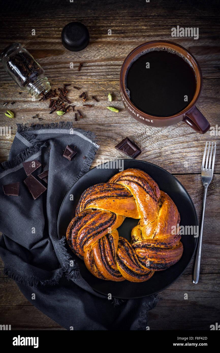 Pastelería dulce y una taza de café negro en vintage mesa de madera, vista superior Imagen De Stock