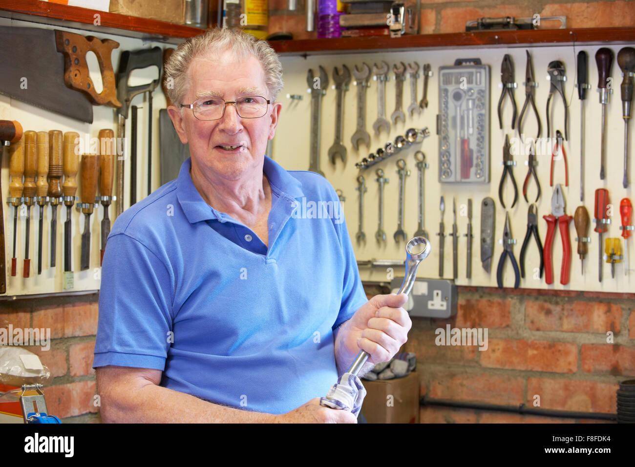 Hombre senior en taller con herramientas permanente Foto de stock