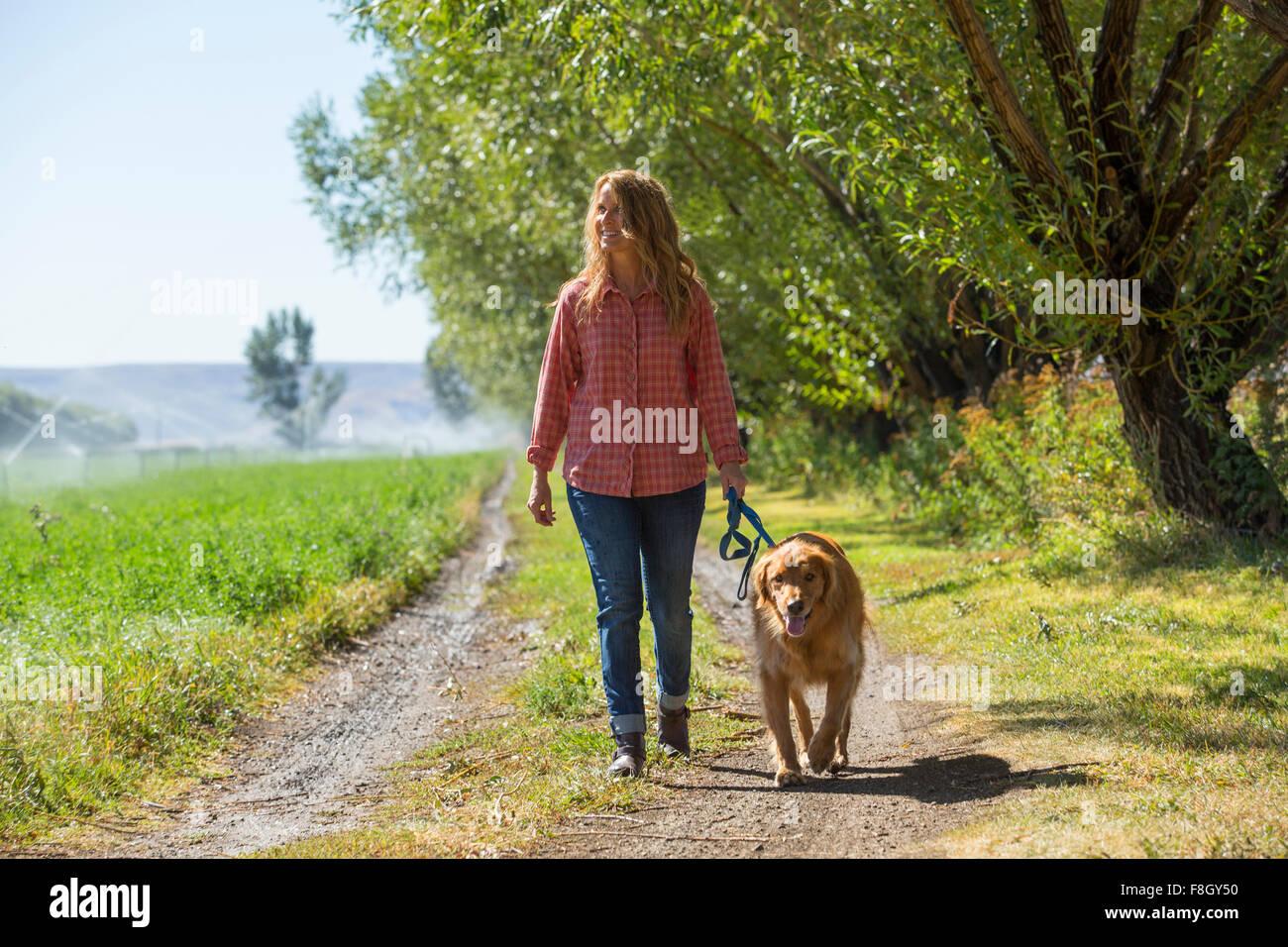 Mujer caucásica caminar perro en camino de tierra Foto de stock