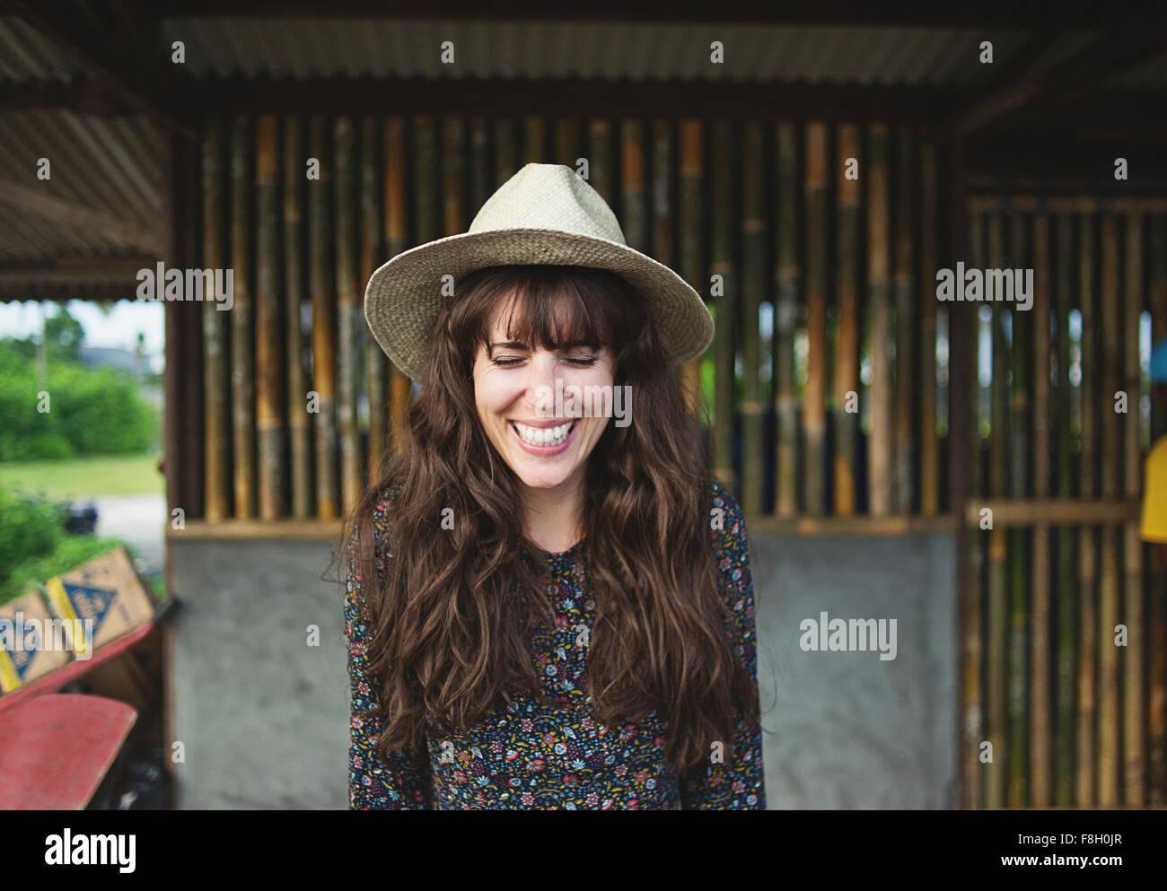 Sonriente mujer caucásica llevar sombrero para el sol al aire libre Foto de stock