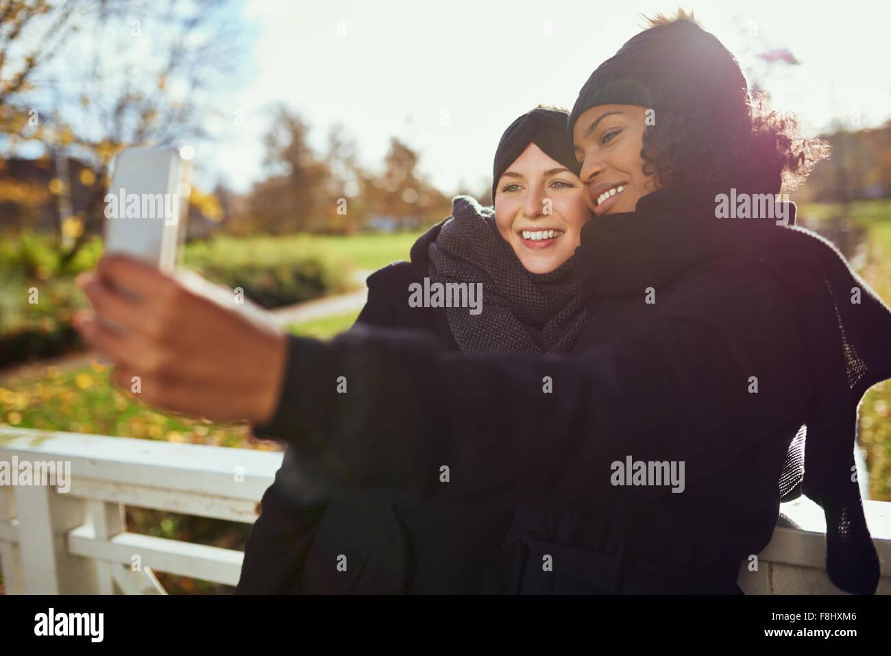 Dos sonriente joven mujer en ropa de abrigo teniendo selfie contra del parque otoñal Imagen De Stock