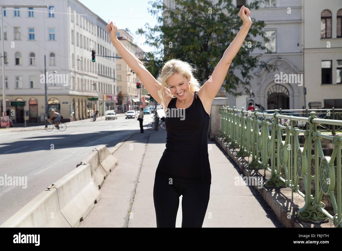 Mujer madura afuera, vistiendo ropa deportiva brazos levantados mirando sonriendo Imagen De Stock
