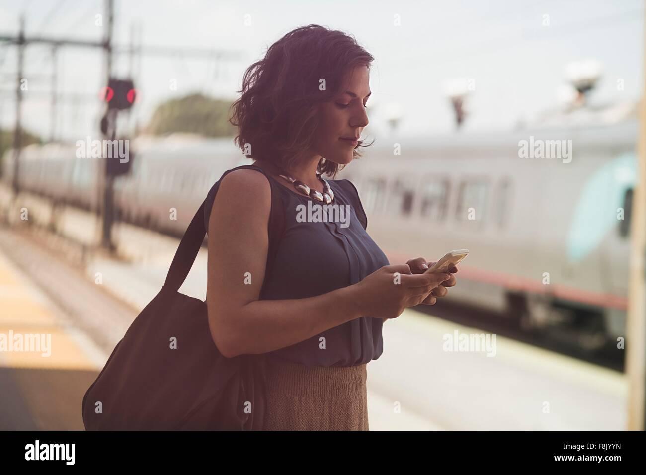 Mujer adulta media esperando en la estación de tren, sujetando el smartphone Imagen De Stock