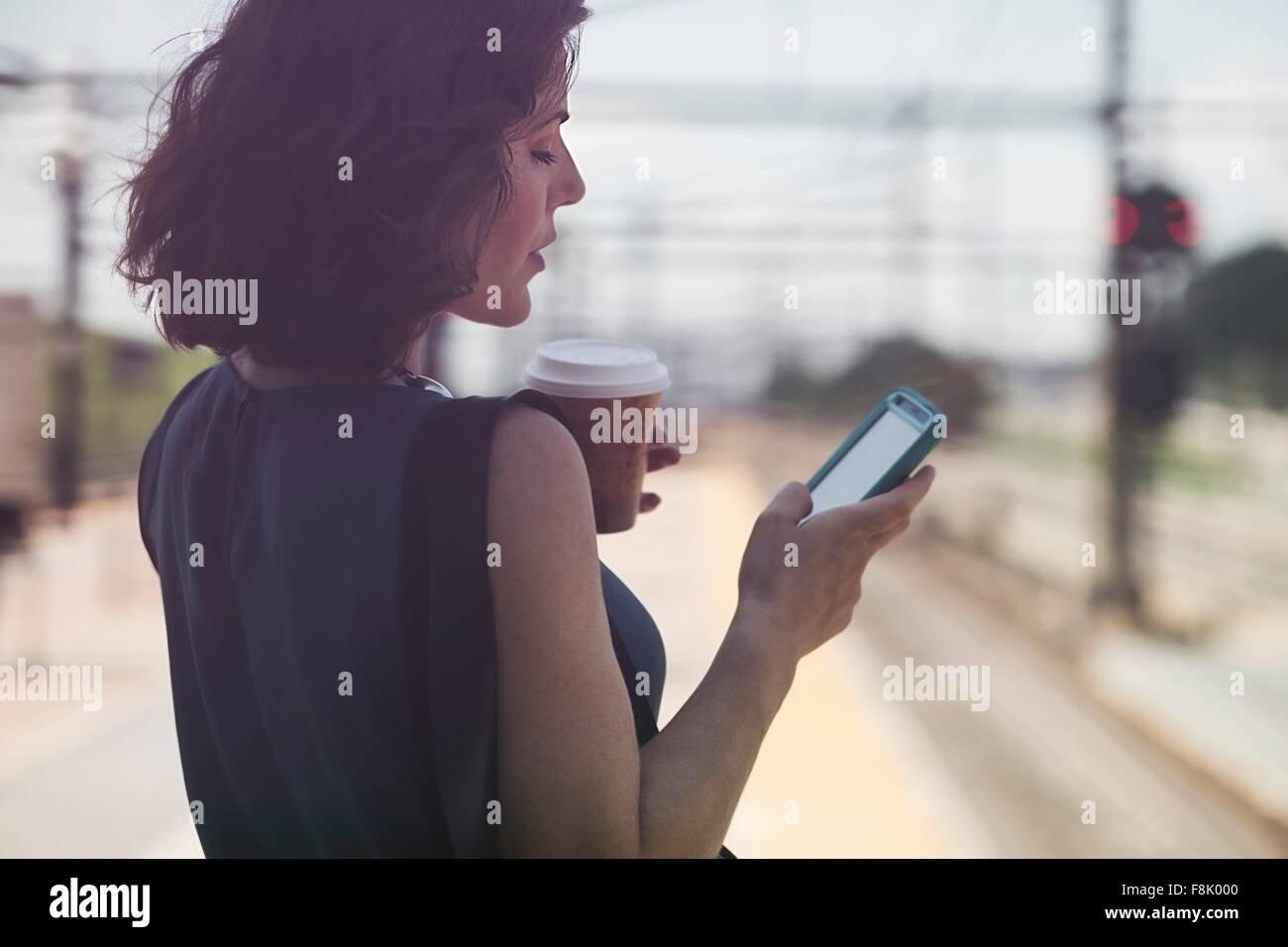 Mujer adulta media esperando en la estación de tren, con smartphone, sosteniendo la taza de café Imagen De Stock