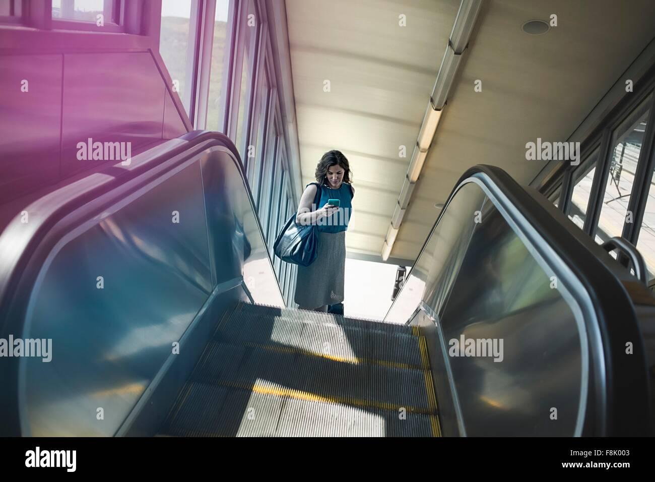 Mujer adulta media mediante escaleras mecánicas, sujetando el smartphone, vista elevada Imagen De Stock