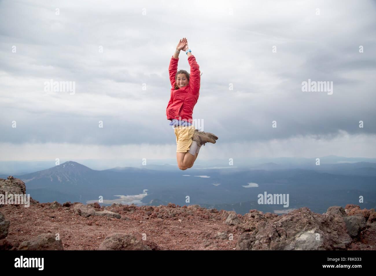 Mujer joven salta de alegría en la cumbre del volcán, hermana de South Bend, Oregon, EE.UU. Imagen De Stock