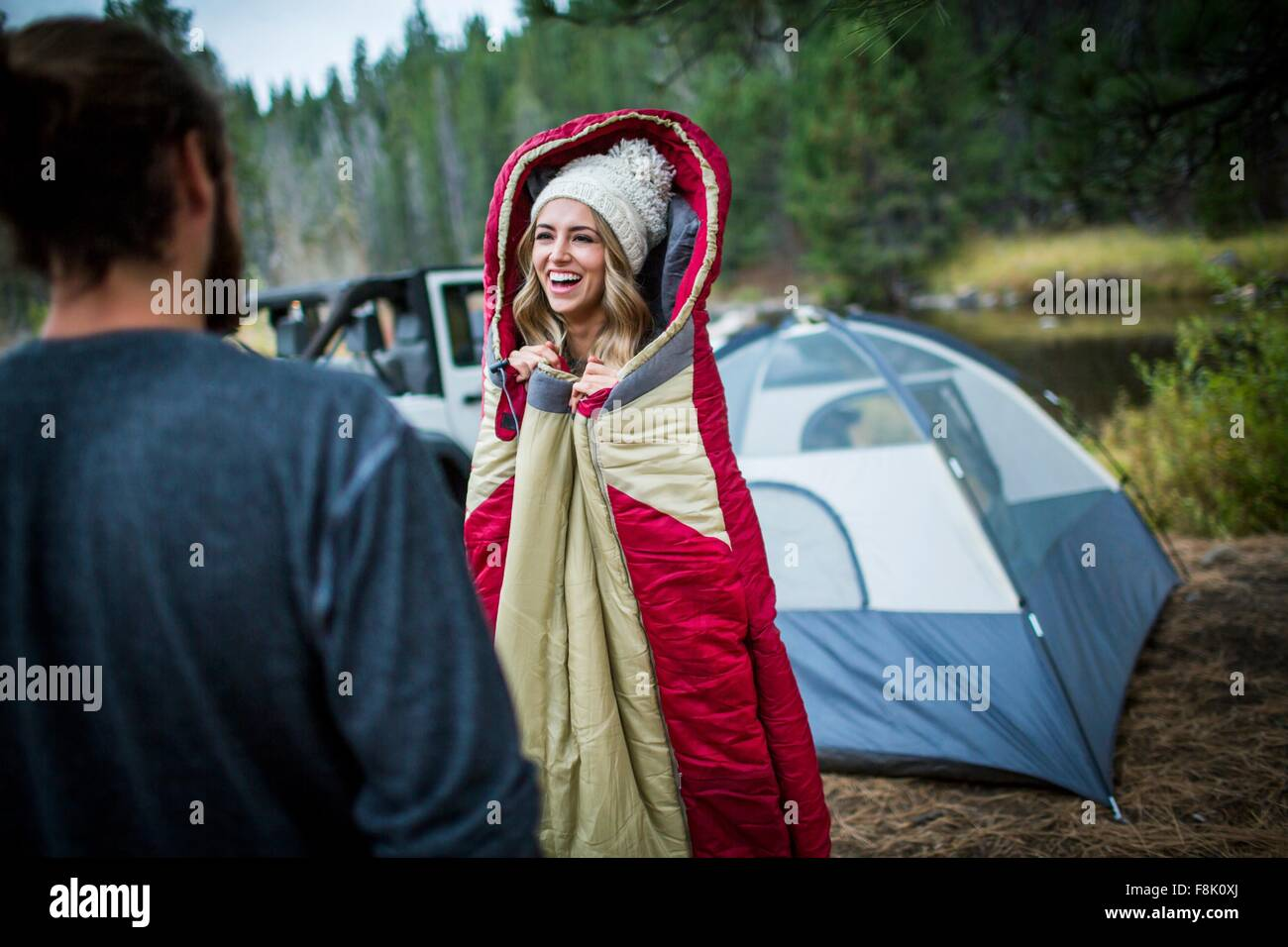 Joven mujer vistiendo knit hat envuelto en saco de dormir, Lake Tahoe, Nevada, EE.UU. Imagen De Stock