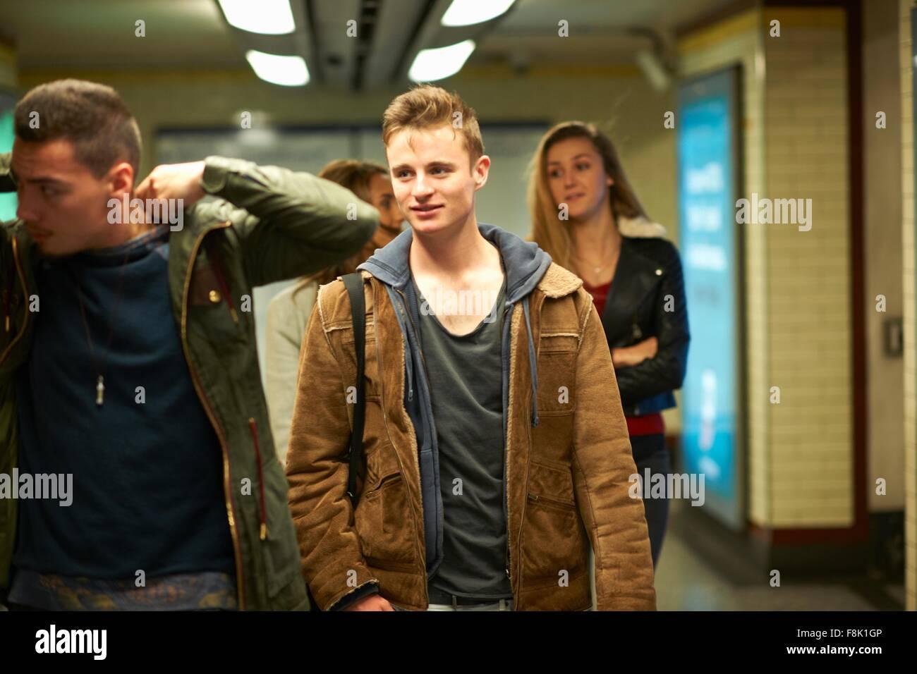 Cuatro jóvenes amigos adultos caminando por la estación del metro de Londres, Londres, Reino Unido. Foto de stock