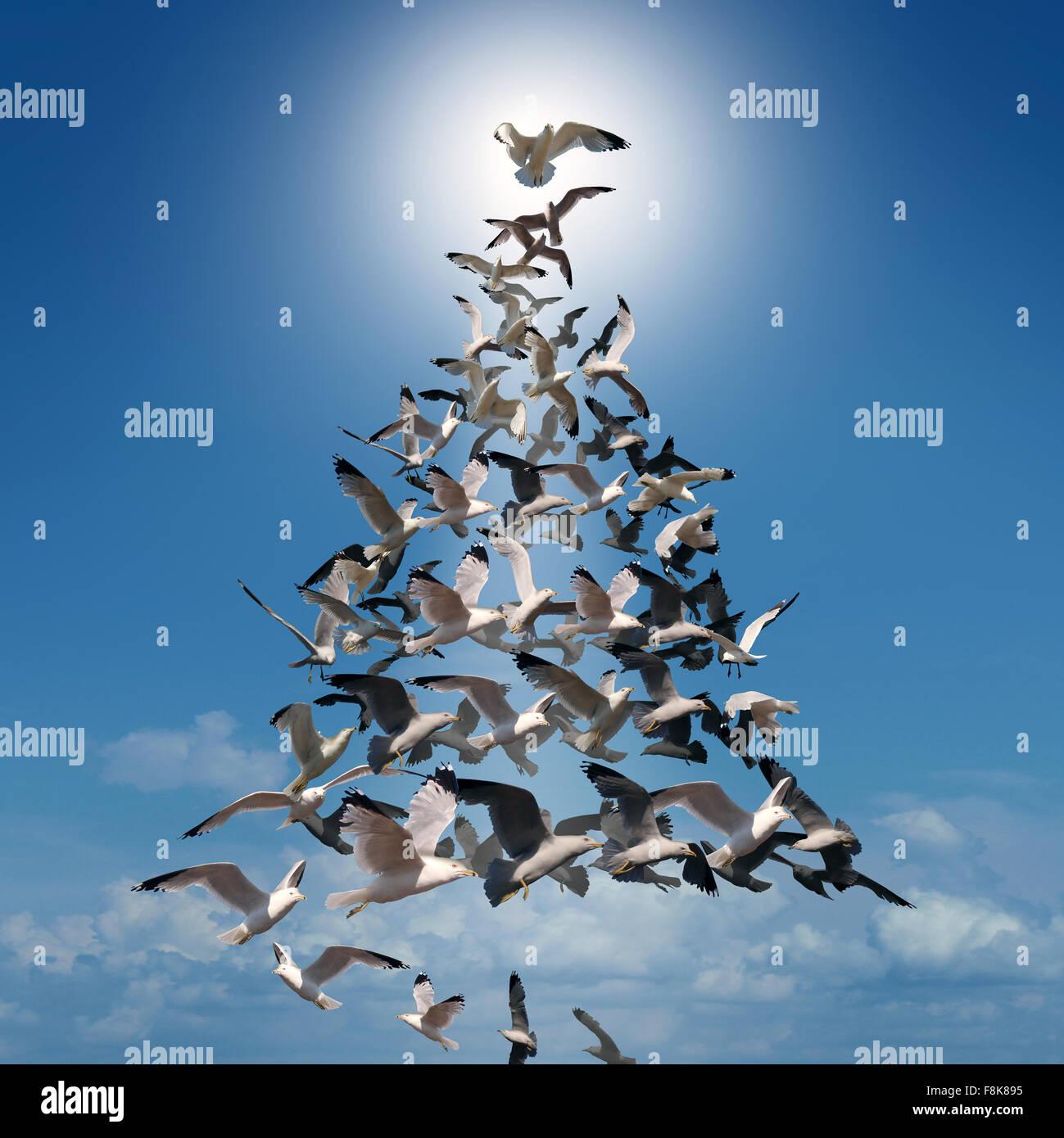 Árbol de Navidad de esperanza concepto espiritual como un grupo de aves volando en estilo coordinado en forma Imagen De Stock