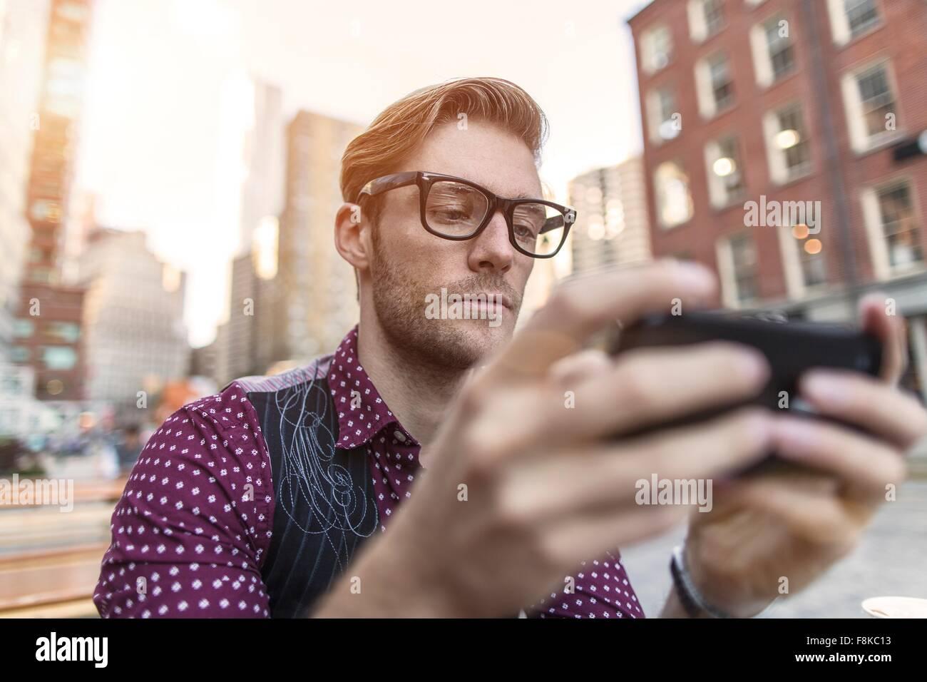 Joven empresario serio smartphone leer texto en café en la acera, Nueva York, EE.UU. Imagen De Stock