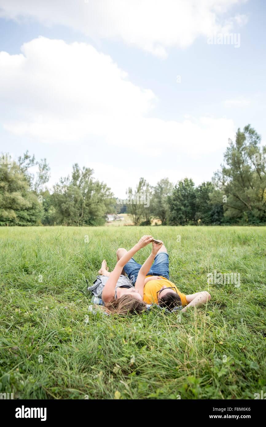 Pareja joven tumbado en la hierba del campo, teniendo autorretrato con el smartphone Imagen De Stock
