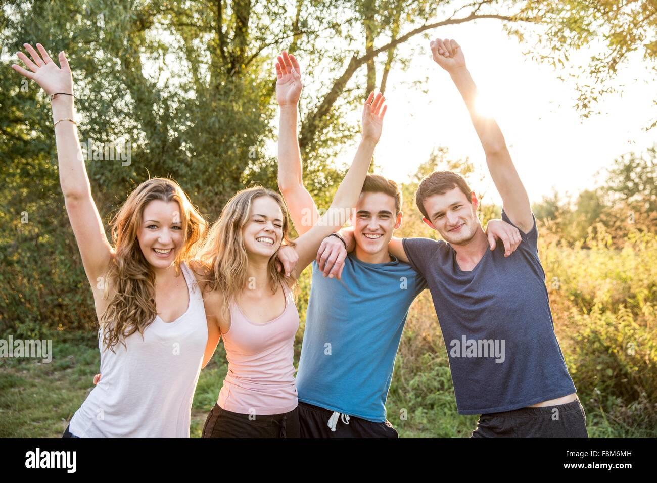 Retrato de un grupo de amigos en el medio rural, con los brazos en alto, sonriendo Imagen De Stock