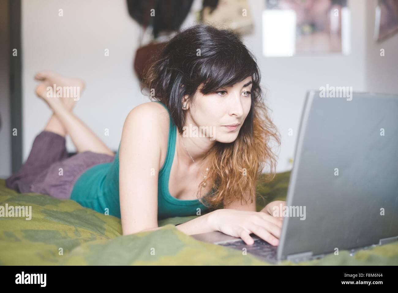 Mujer joven tumbado en la parte delantera de la cama mediante ordenador portátil Imagen De Stock