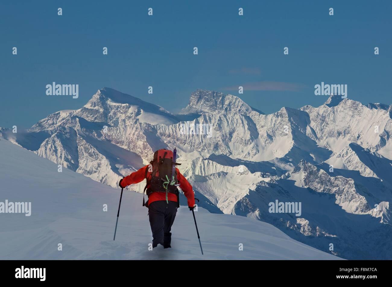 Vista trasera de escalador sube a través de nieve profunda, Alpes Suizos, Cantón Wallis, Suiza Imagen De Stock