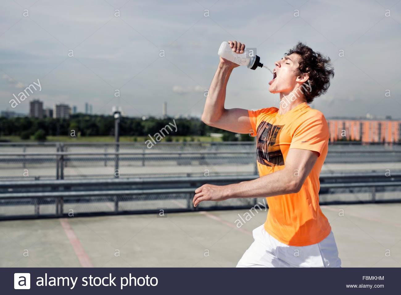 Macho joven corredor agua potable mientras ejecuta la ciudad Imagen De Stock