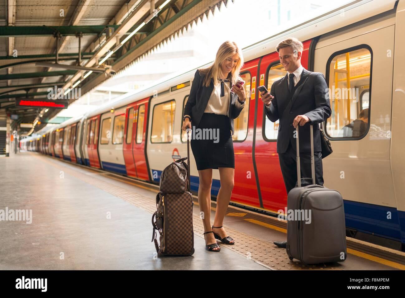 Empresario y empresaria texting sobre la plataforma, a la estación de metro, Londres, Reino Unido. Imagen De Stock