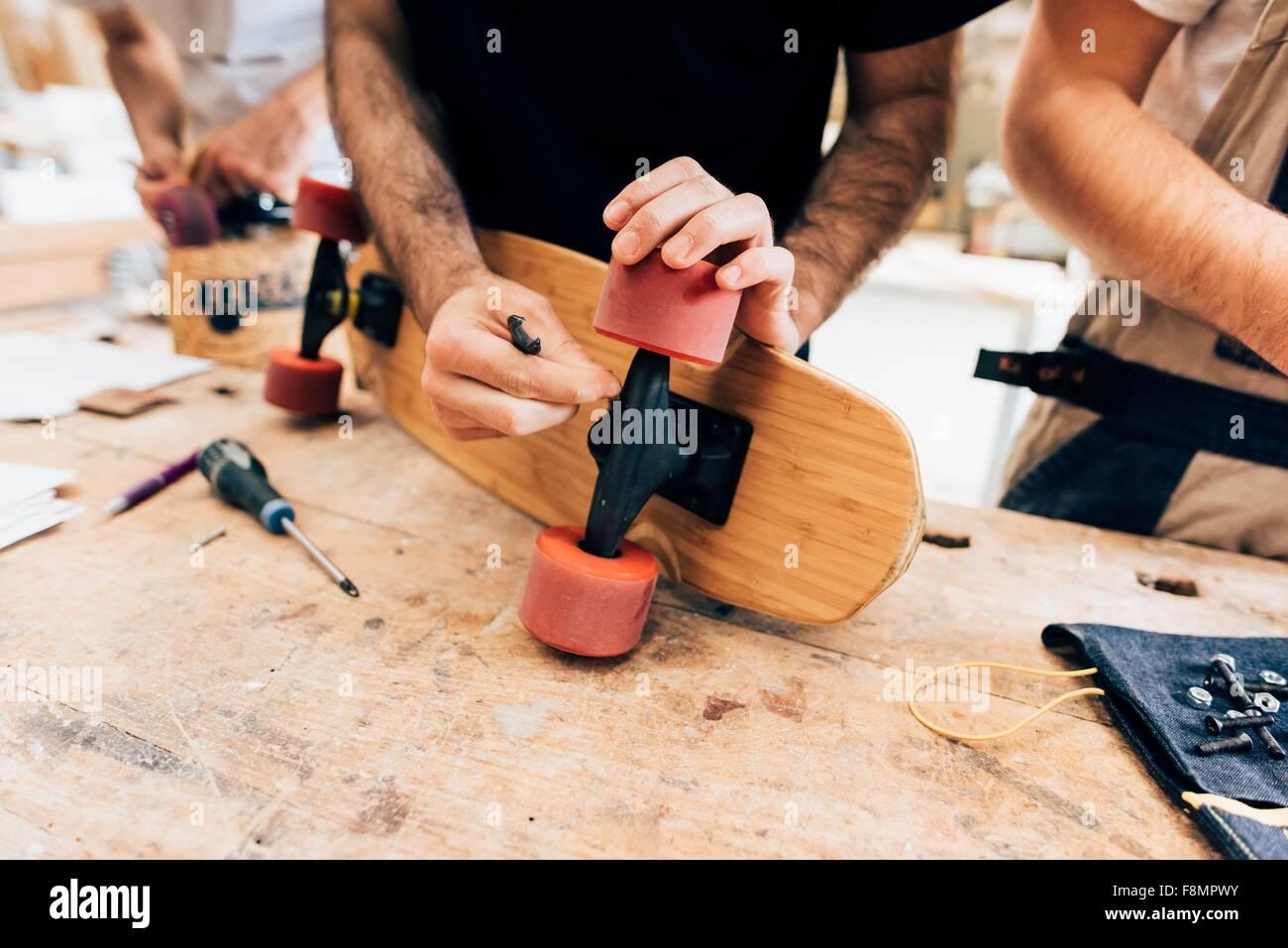 Vista recortada de hombres jóvenes en taller de fijación de ruedas de monopatín Imagen De Stock