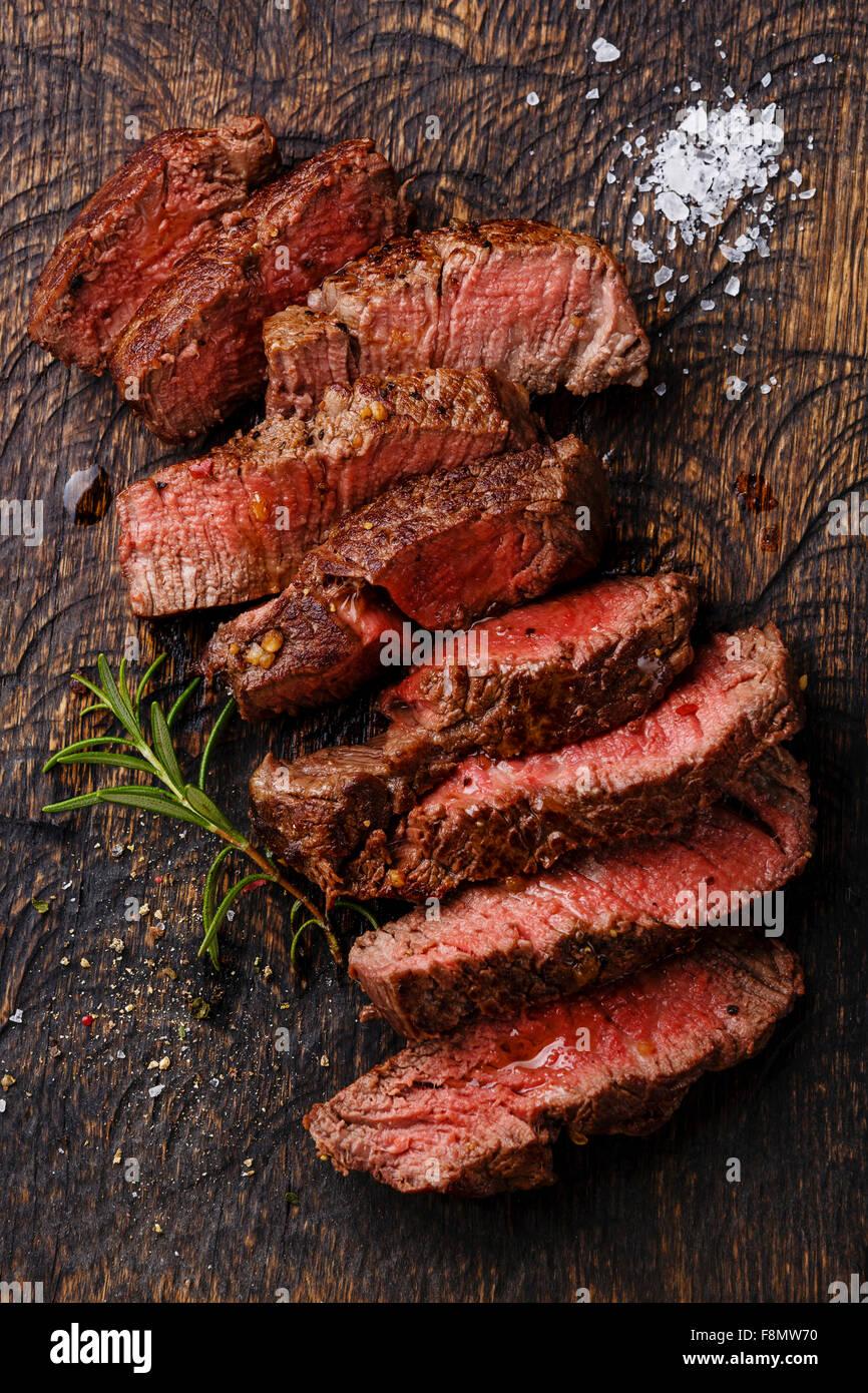 Medio raro lonchas de carne asada steak en la tabla de cortar de madera antecedentes Imagen De Stock