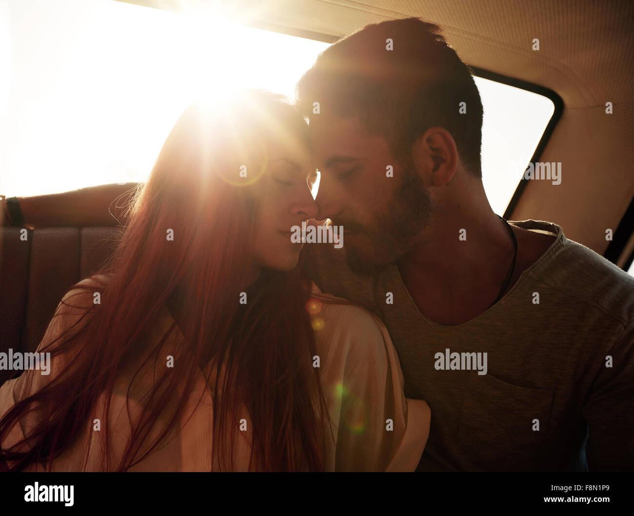 Romántica pareja joven sentado en el asiento trasero de un coche. Pareja joven sentimiento romántico en Imagen De Stock