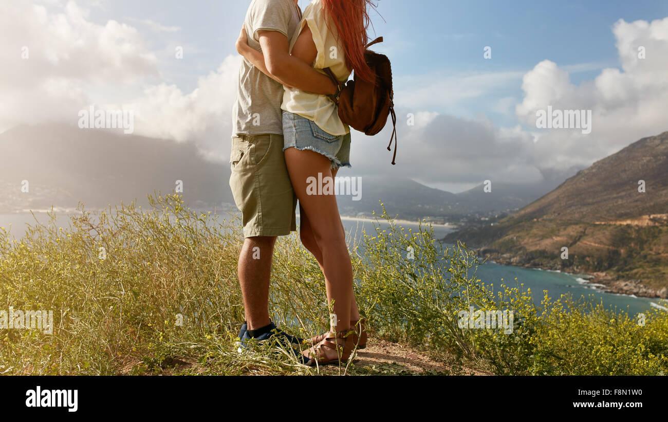 Imagen recortada de amorosa pareja joven abrazando mientras está de pie sobre un acantilado en la costa. Bajo Imagen De Stock