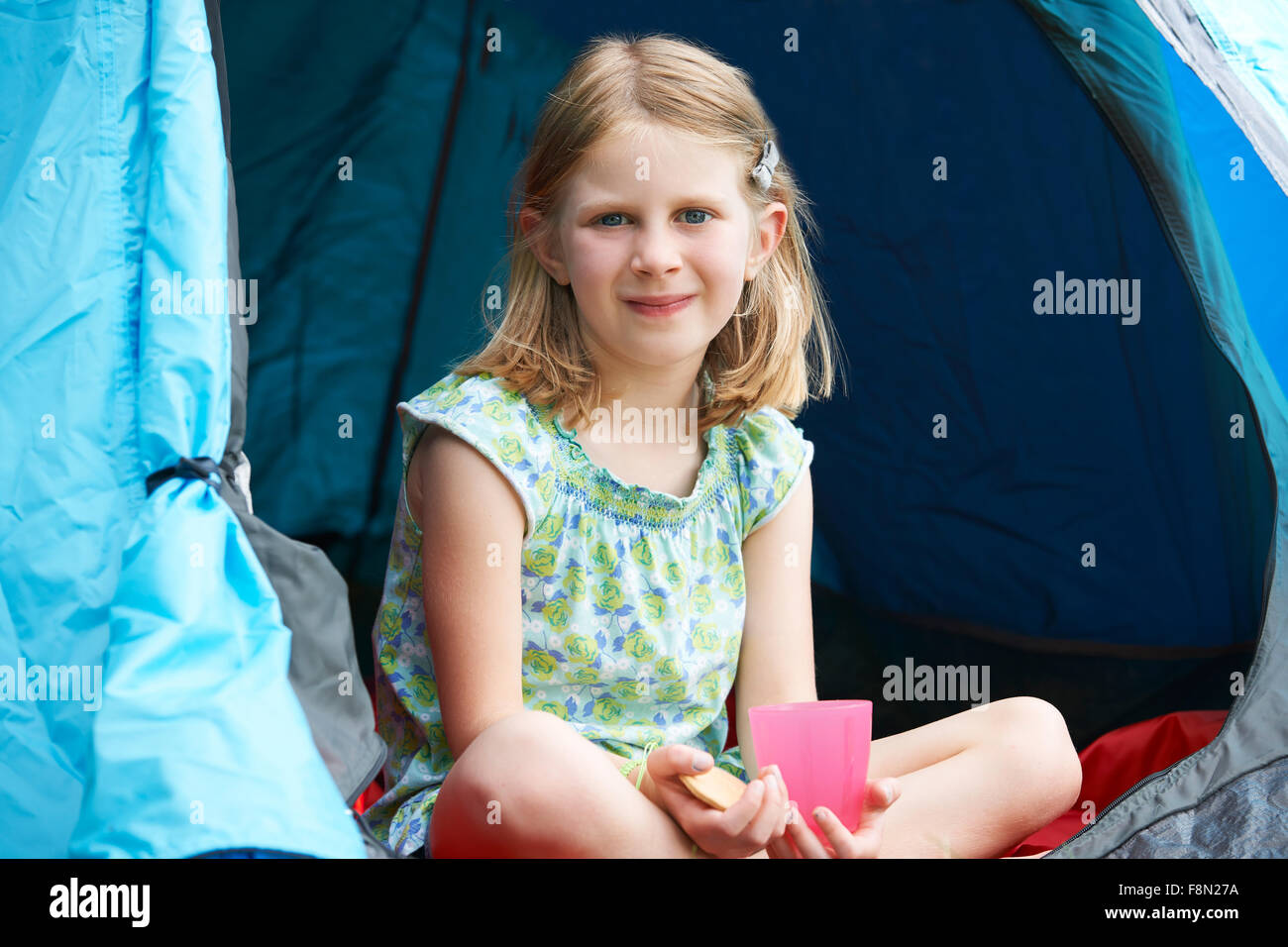 Chica tener un bocadillo en camping Imagen De Stock