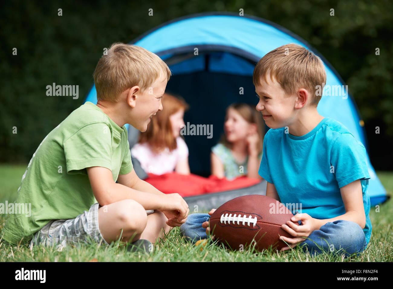 Dos chicos hablando y jugando con el fútbol americano en camping Imagen De Stock
