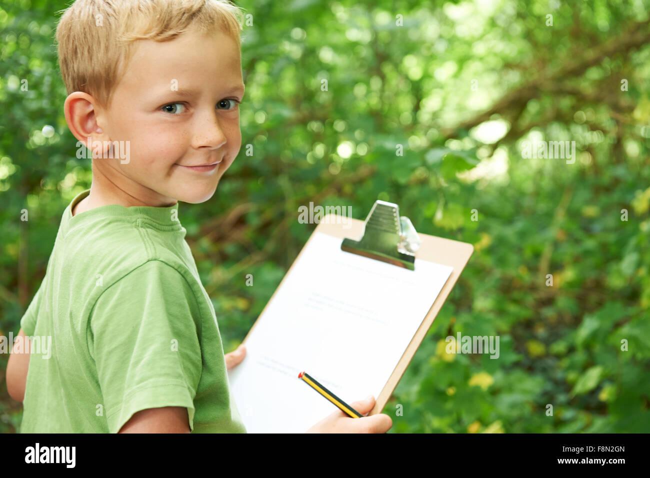 Boy haciendo notas sobre la Escuela Naturaleza viaje de campo Imagen De Stock