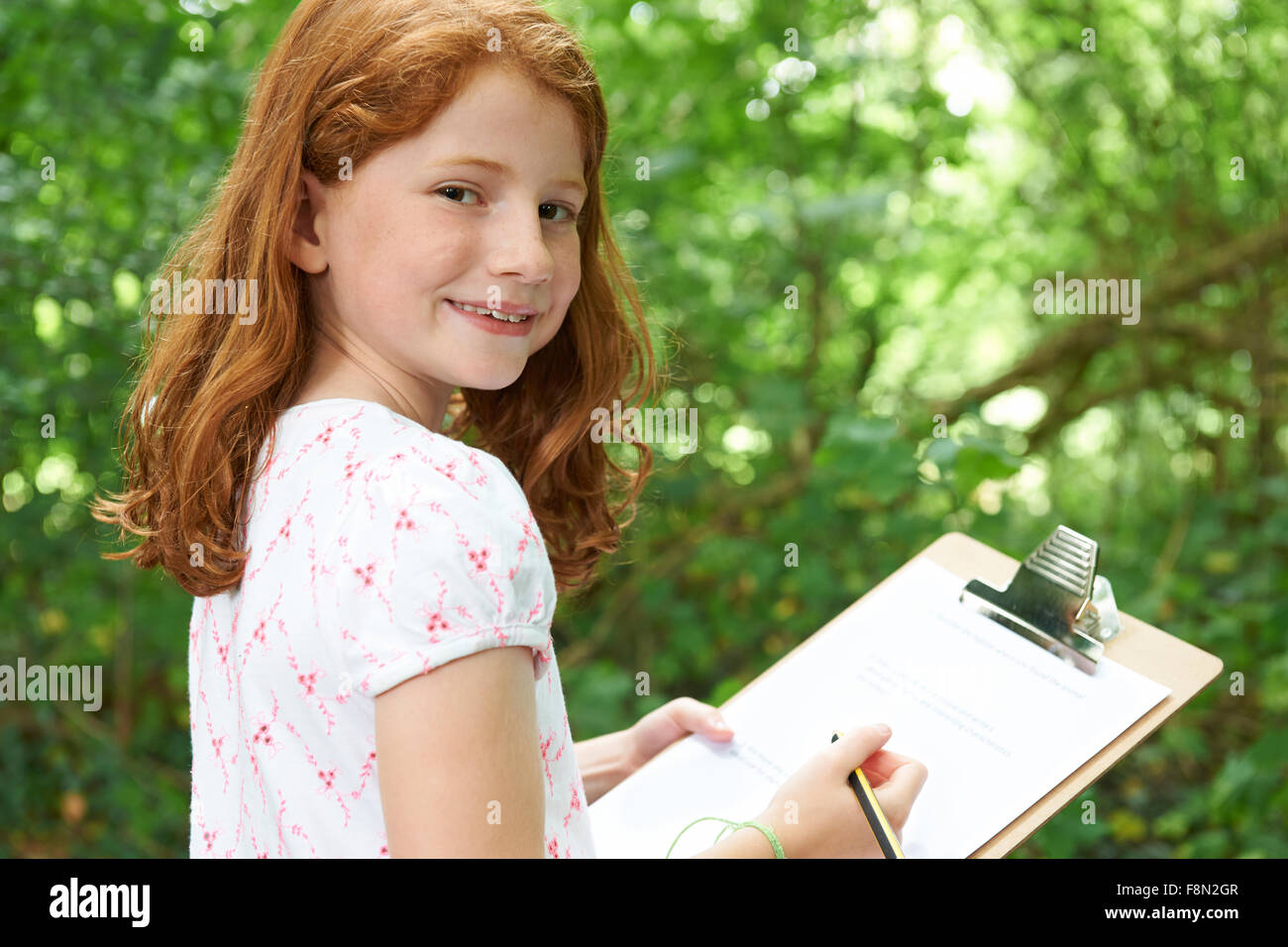 Chica haciendo notas sobre la Escuela Naturaleza viaje de campo Imagen De Stock